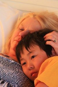 Blonde white mother and Asian child snuggling