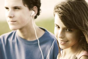 Two teens sharing music on headphones